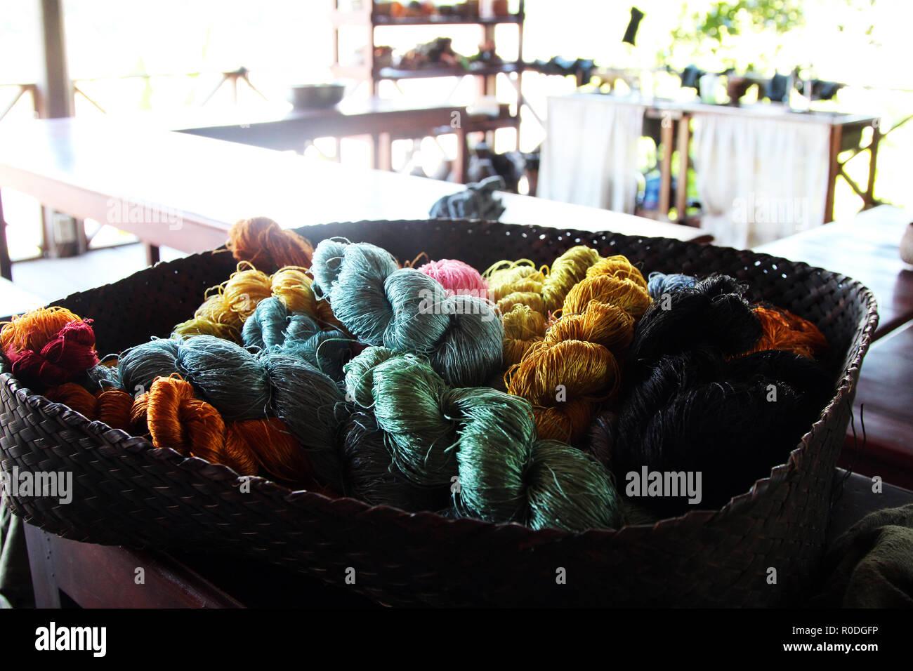 Basket of naturally dyed silk skeins for weaving, Ok Pop Tok weaving center, Luang Prabang, Laos - Stock Image