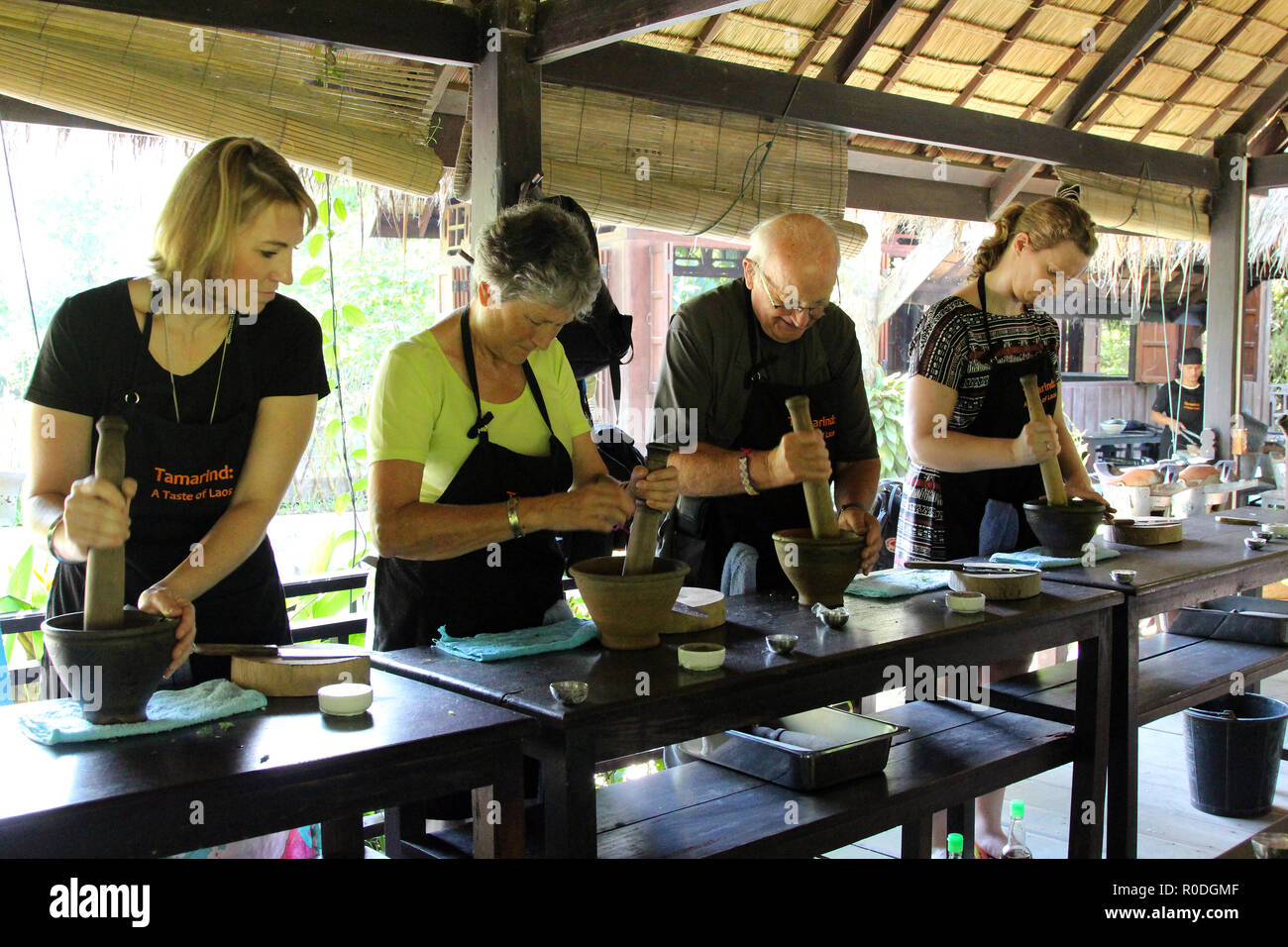 Students in a Laotian cooking class mash their ingredients, Tamarind Cooking School, Luang Prabang, Laos - Stock Image