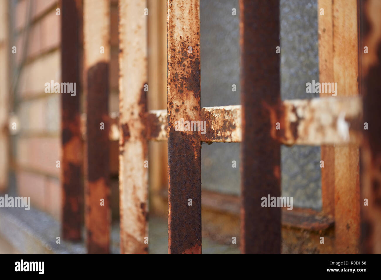 Detail of a rusty and corroded window bar: an example of the corrosion of iron under the effect of bad weather and air. - Stock Image