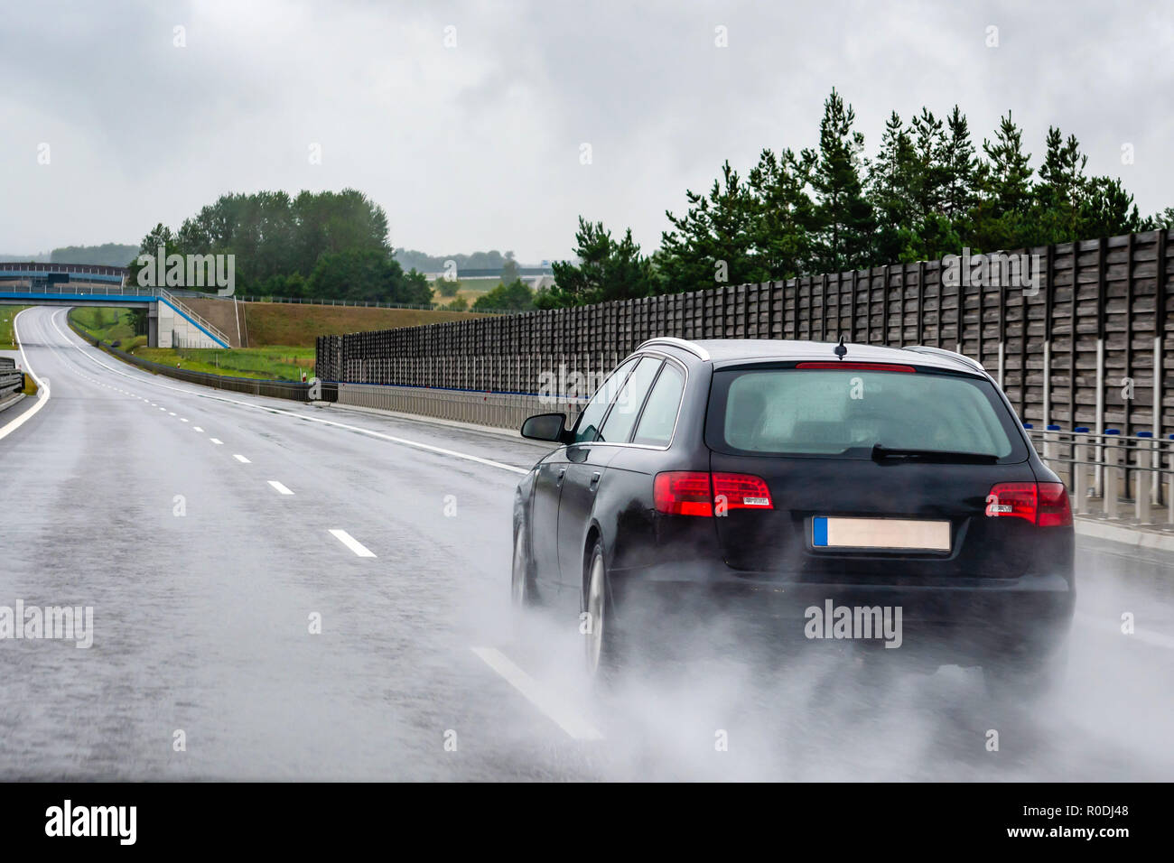 A car on a wet road in the rain. View from the rear through the car window. Stock Photo