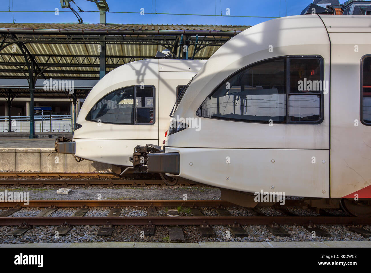 Two light rail trains on Central Station in Groningen waiting at the platform to leave for Delfzijl. The light rail trains are an easy and comfortable - Stock Image