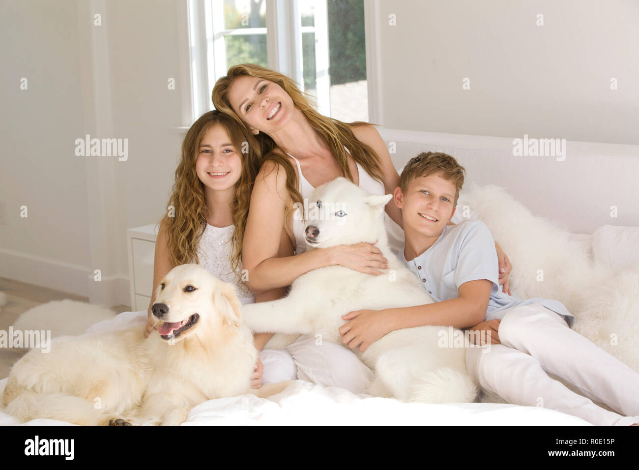 Happy Family Portrait of Mother with Two Young Children and Pet Dogs I - Stock Image