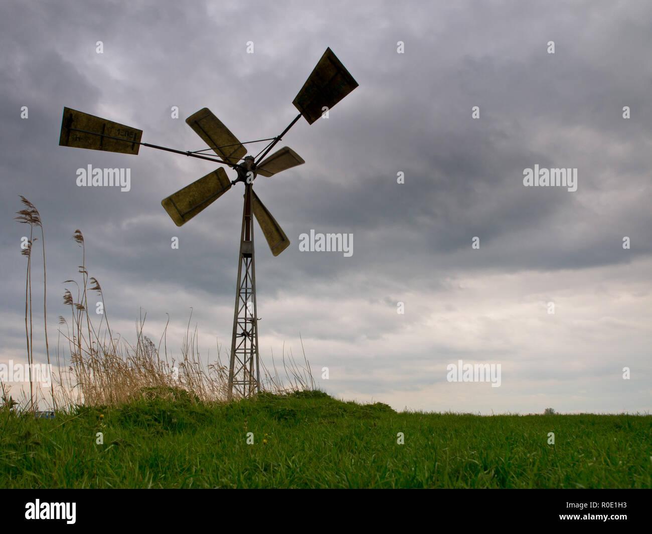 Een Amerikaanse windmolen onder een dreigende stormachtige lucht Stock Photo
