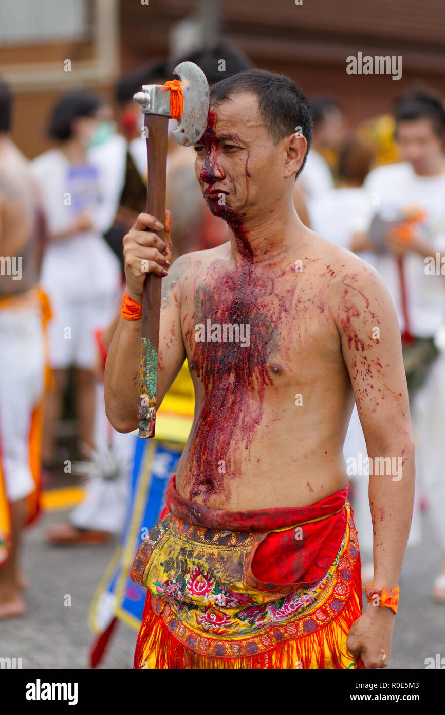 PHUKET TOWN, THAILAND, OCTOBER 09, 2016 : Taoist devotees self harming with an axe for purification during vegetarian festival in Phuket town, Thailan - Stock Image