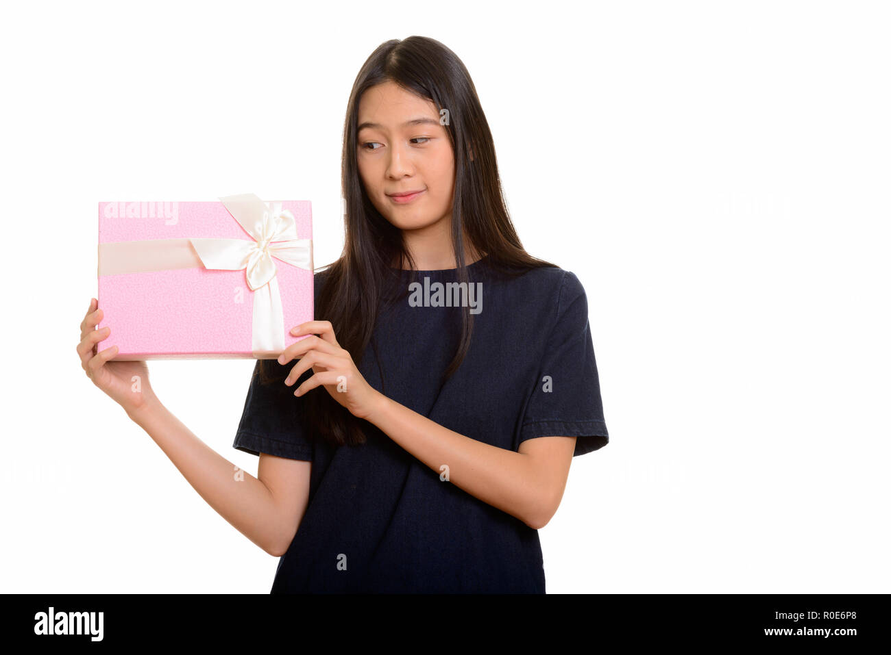 Young beautiful Asian teenage girl guessing gift box - Stock Image