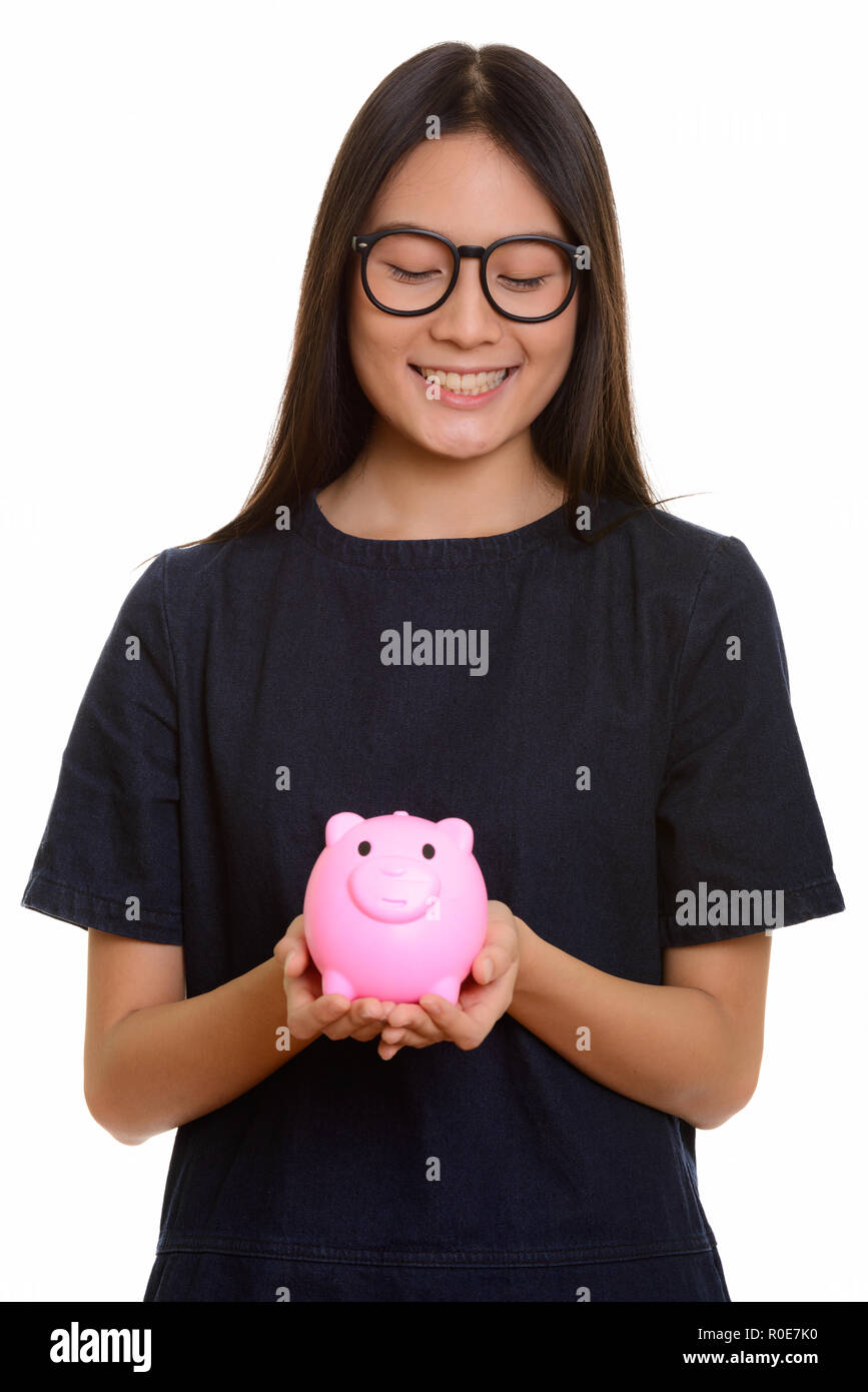 Young happy Asian teenage girl smiling and holding piggy bank - Stock Image