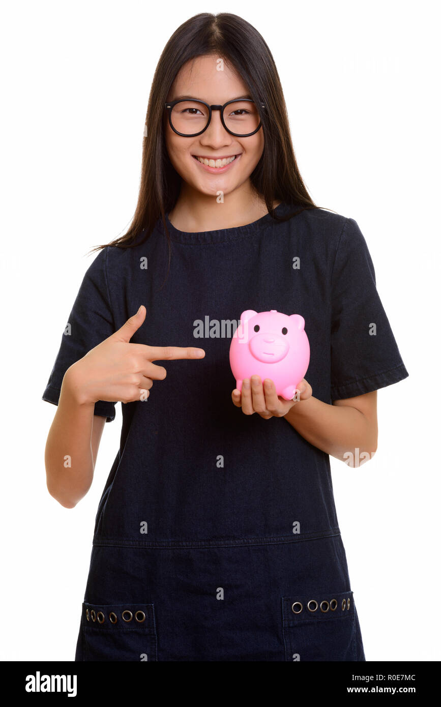 Young happy Asian teenage girl smiling while pointing finger and - Stock Image