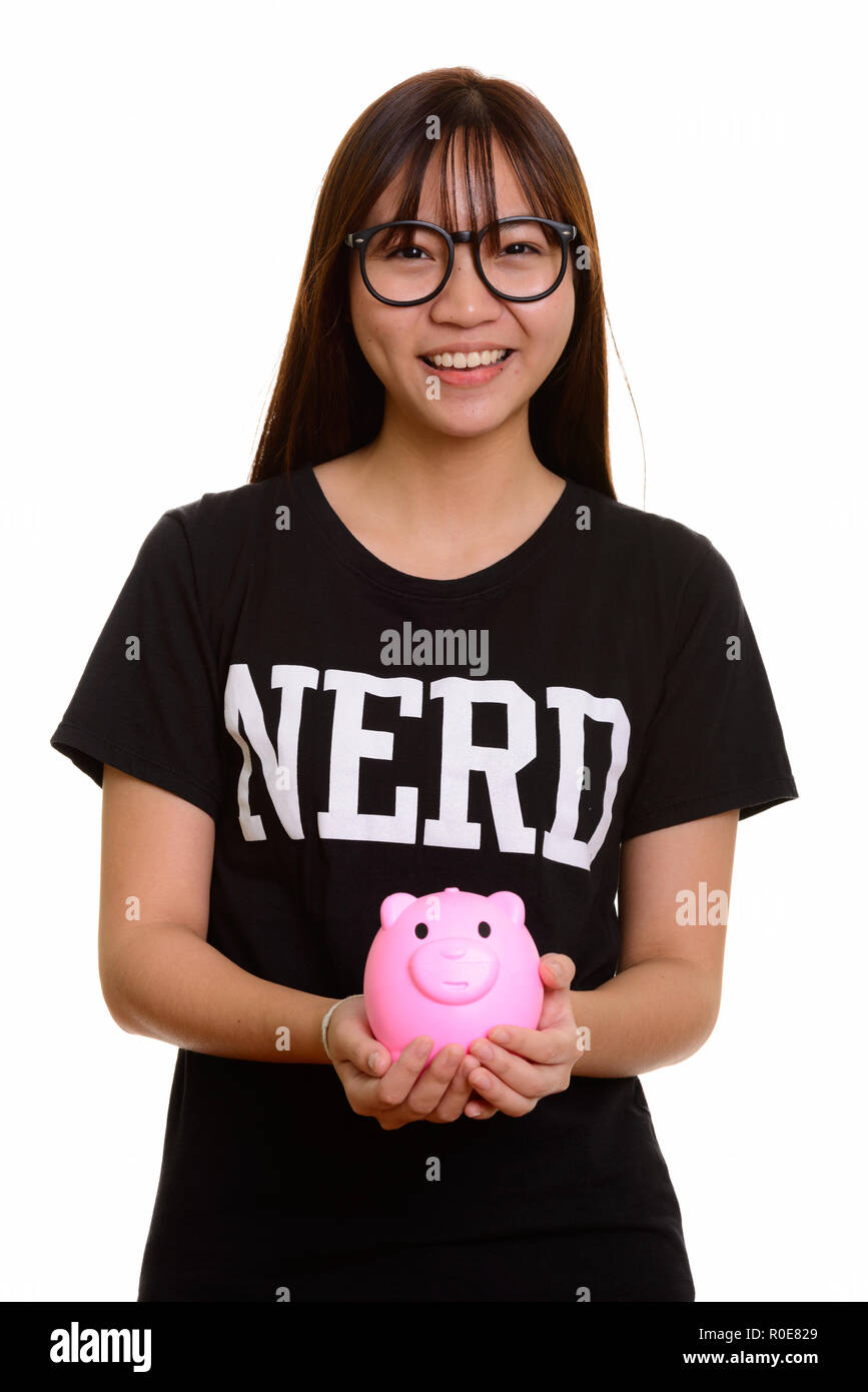 Young happy Asian nerd teenage girl smiling and holding piggy ba - Stock Image