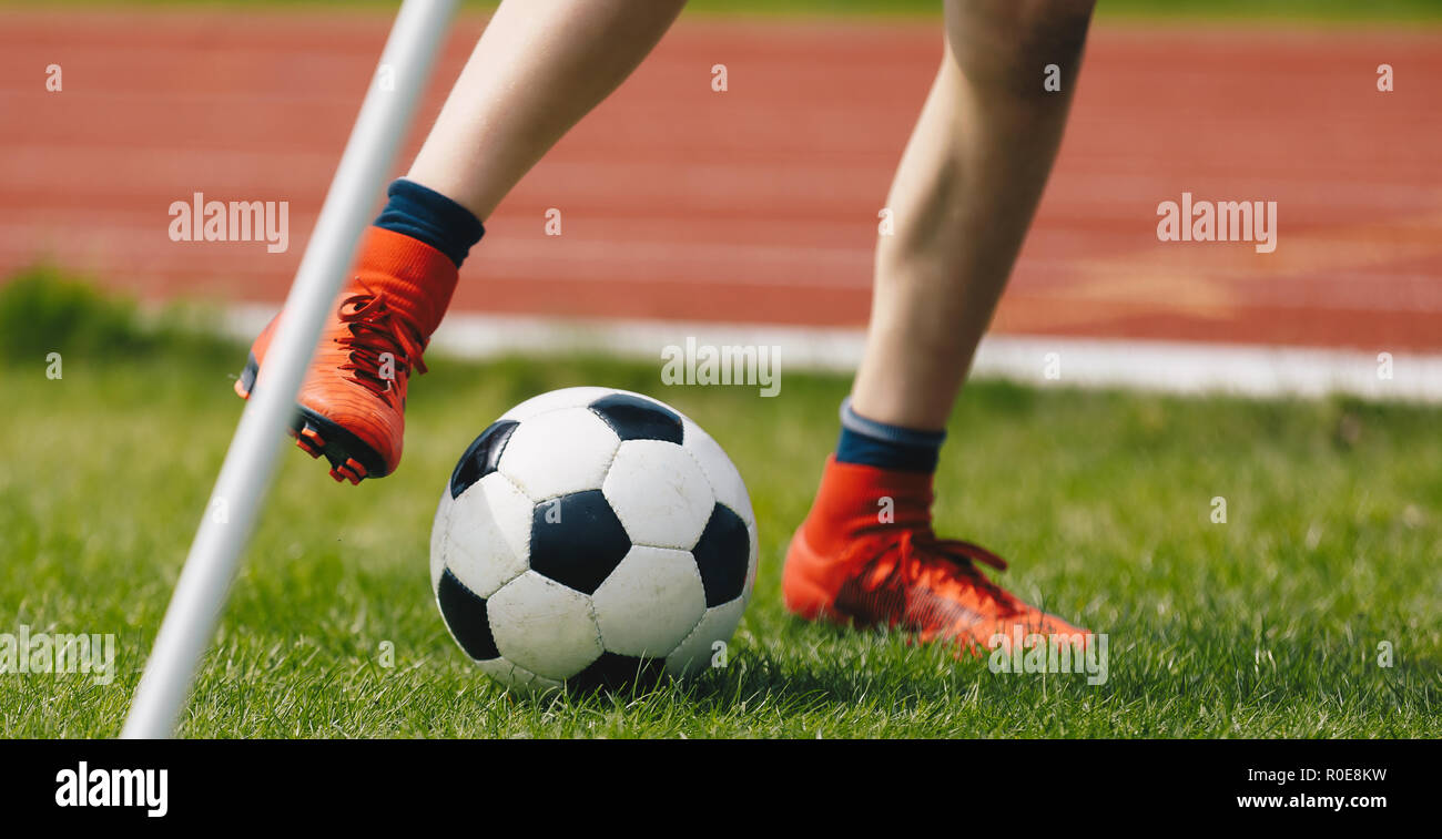 Close-up of Young Soccer Player Kicking Ball on Soccer Field. Football Corner Kick on the Pitch. Footballer in Red Cleats on the Green Lawn of the Sta - Stock Image