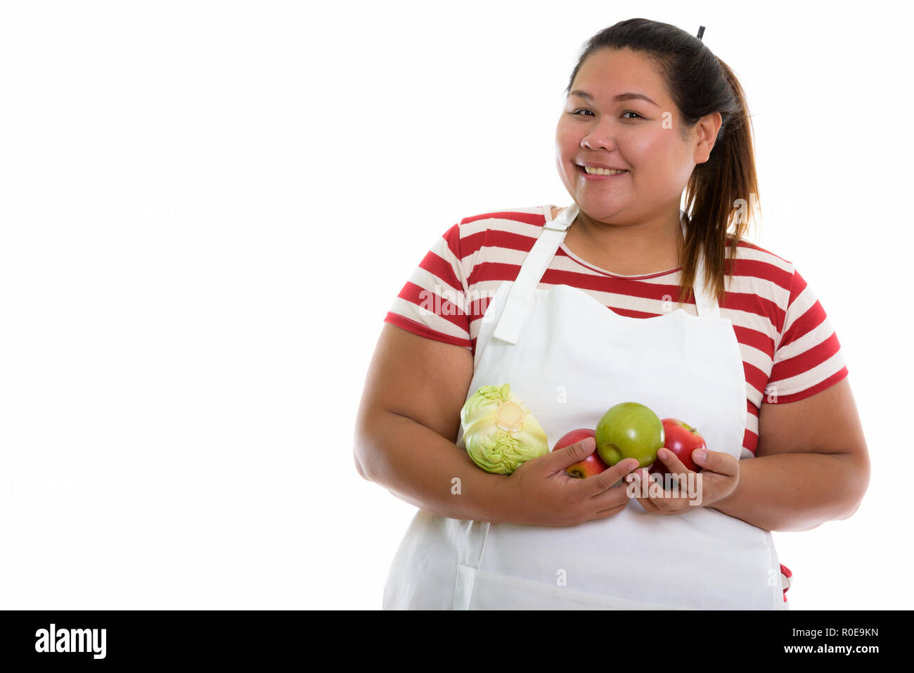 Studio shot of young happy fat Asian woman smiling while holding - Stock Image