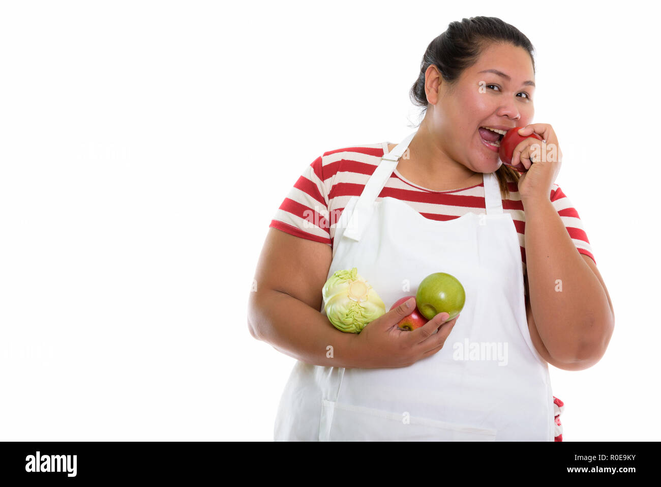 Studio shot of young happy fat Asian woman smiling and eating re - Stock Image