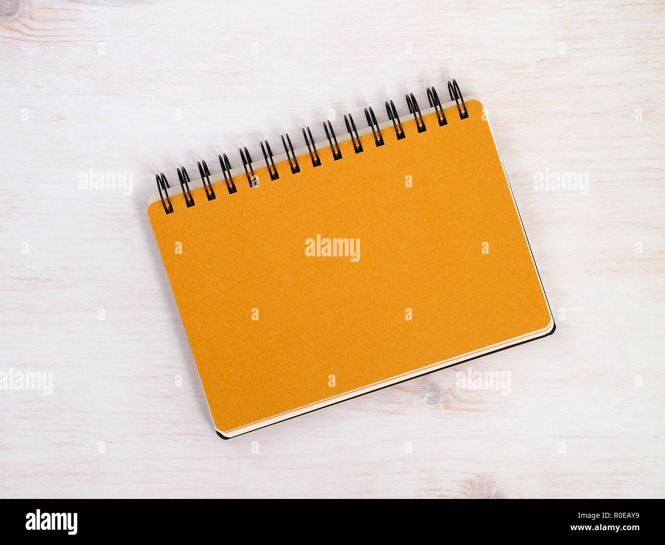 Spiral notebook with orange page divider on white wooden table. Top view. - Stock Image