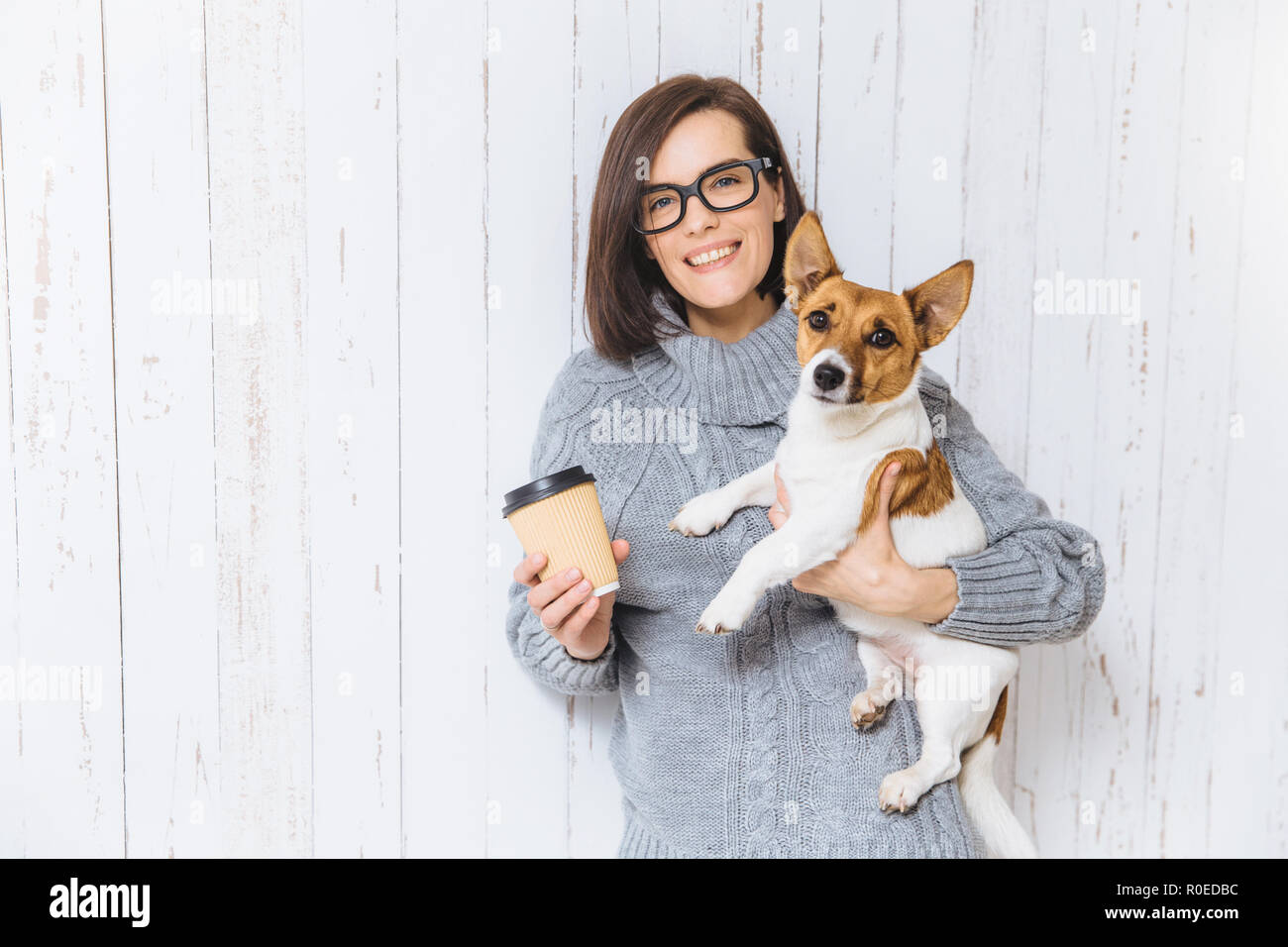 Photo of pleased brunette female carries her favourite dog, drinks hot coffee from paper cup, has pleasant warm smile on face, rejoices nice time spen - Stock Image