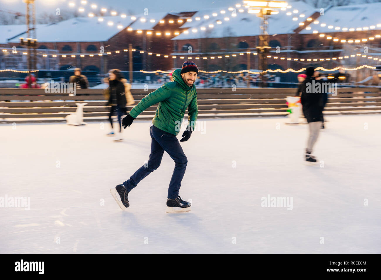 Joyful bearded man practices going skating on ice ring, has cheerful expression, smiles happily, demontrates his professionalism. Active sporty male i - Stock Image