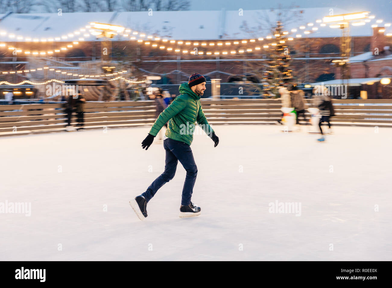 Pleased man in green jacket, wears skates, goes skating on ice, spends winter holidays with use, demonstrates his professionalism, enjoys snowy weathe - Stock Image
