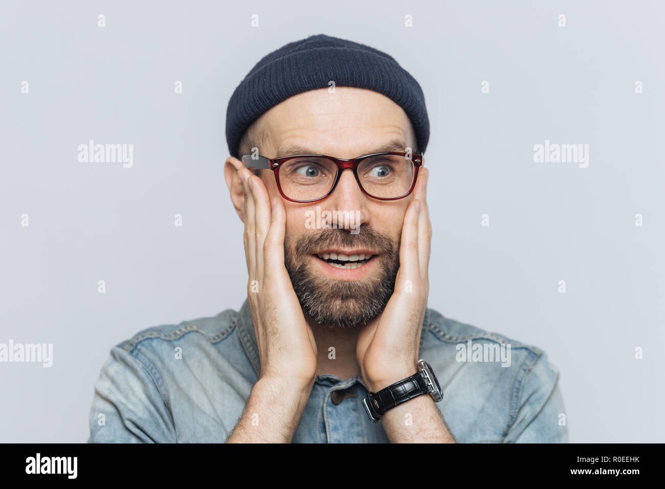Amazed handsome middle aged man looks into distance in bewilderment, keeps hands on cheeks, wears glasses and hat, isolated over white background. Peo - Stock Image