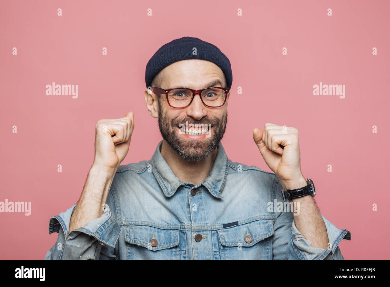 Happy bearded male with blue eyes and cheerful expression clenches fists, feels to be winner, demonstrates positiveness, isolated over pink background - Stock Image