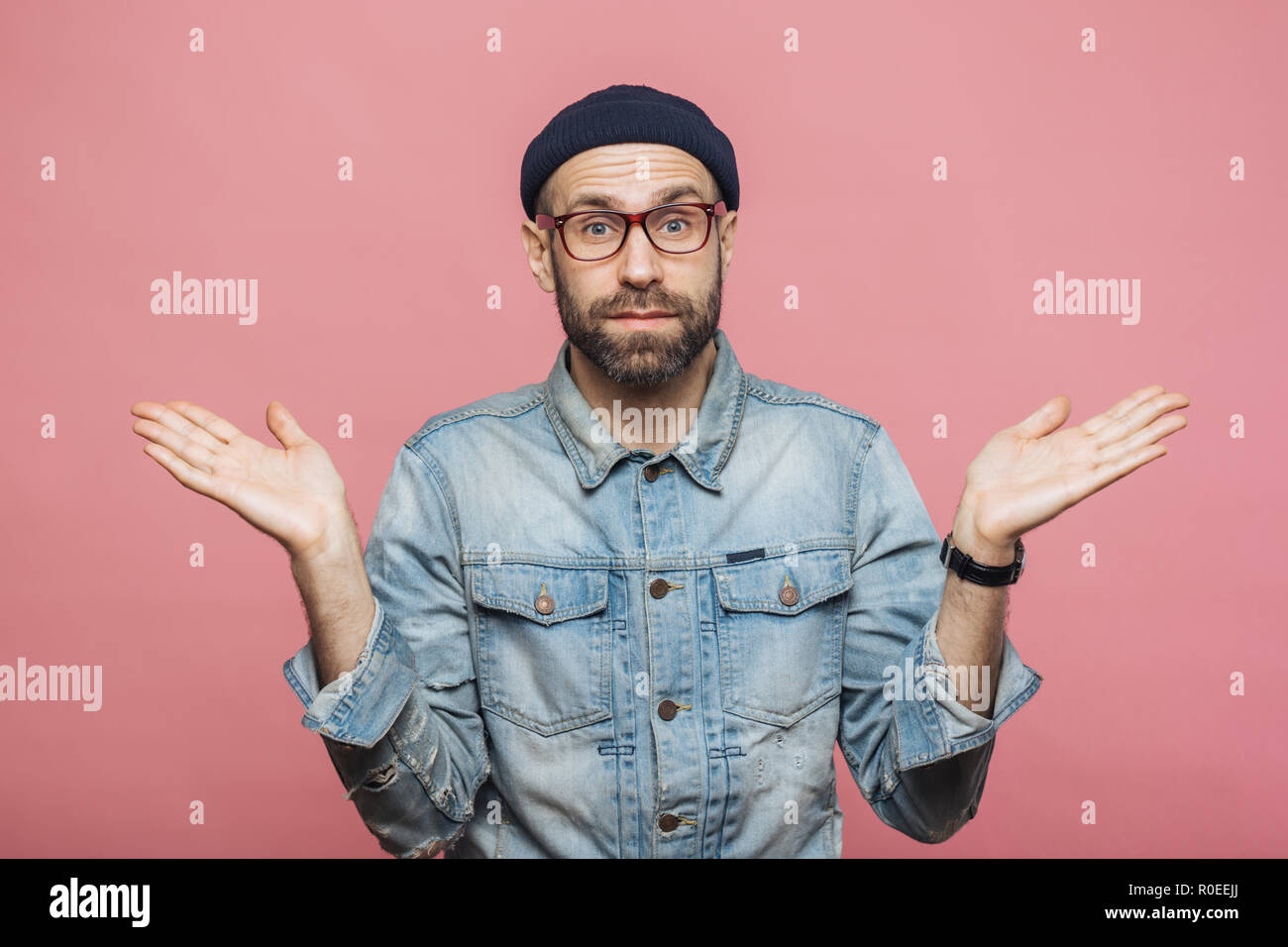 Photo of attractive bearded male wears fashionable clothing, shrugs shoulders in bewilderment, makes serious decision, isolated over pink background.  - Stock Image