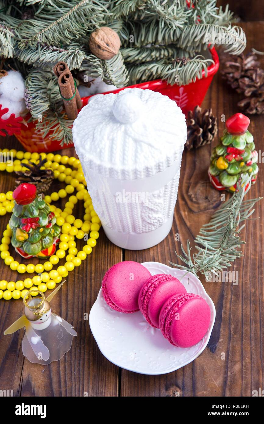 White christmas cup and pink macaroons on wood. Focus on cup - Stock Image