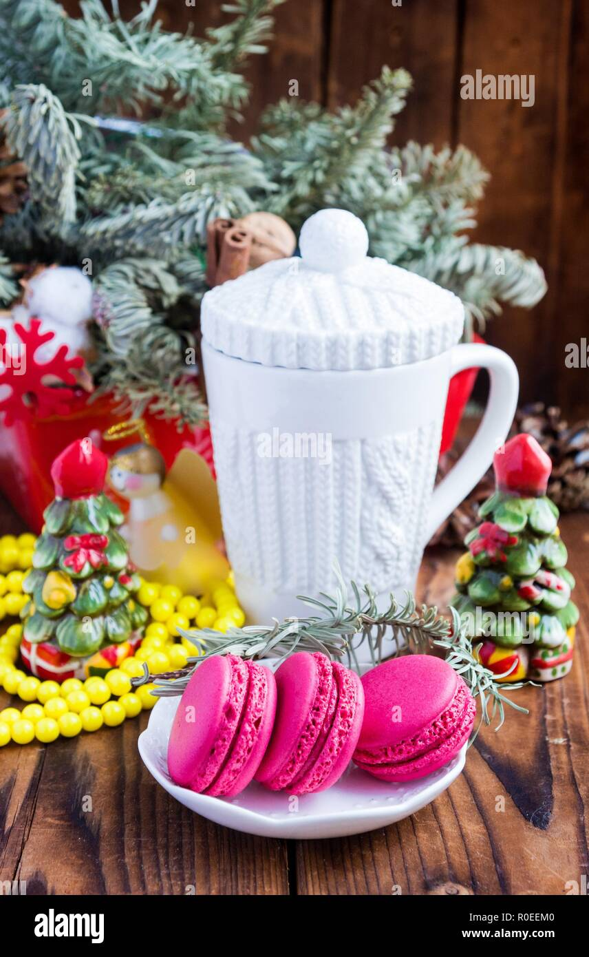 White christmas cup and pink macaroons on wood. Focu on macaroones - Stock Image