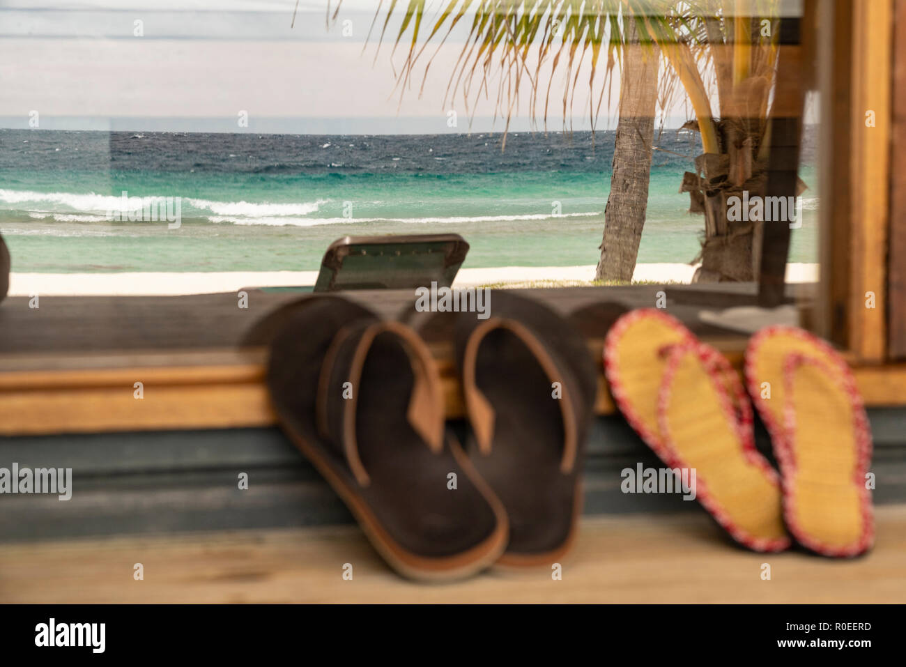 Two pairs of Flip Flops on a porch at the Maledives. - Stock Image