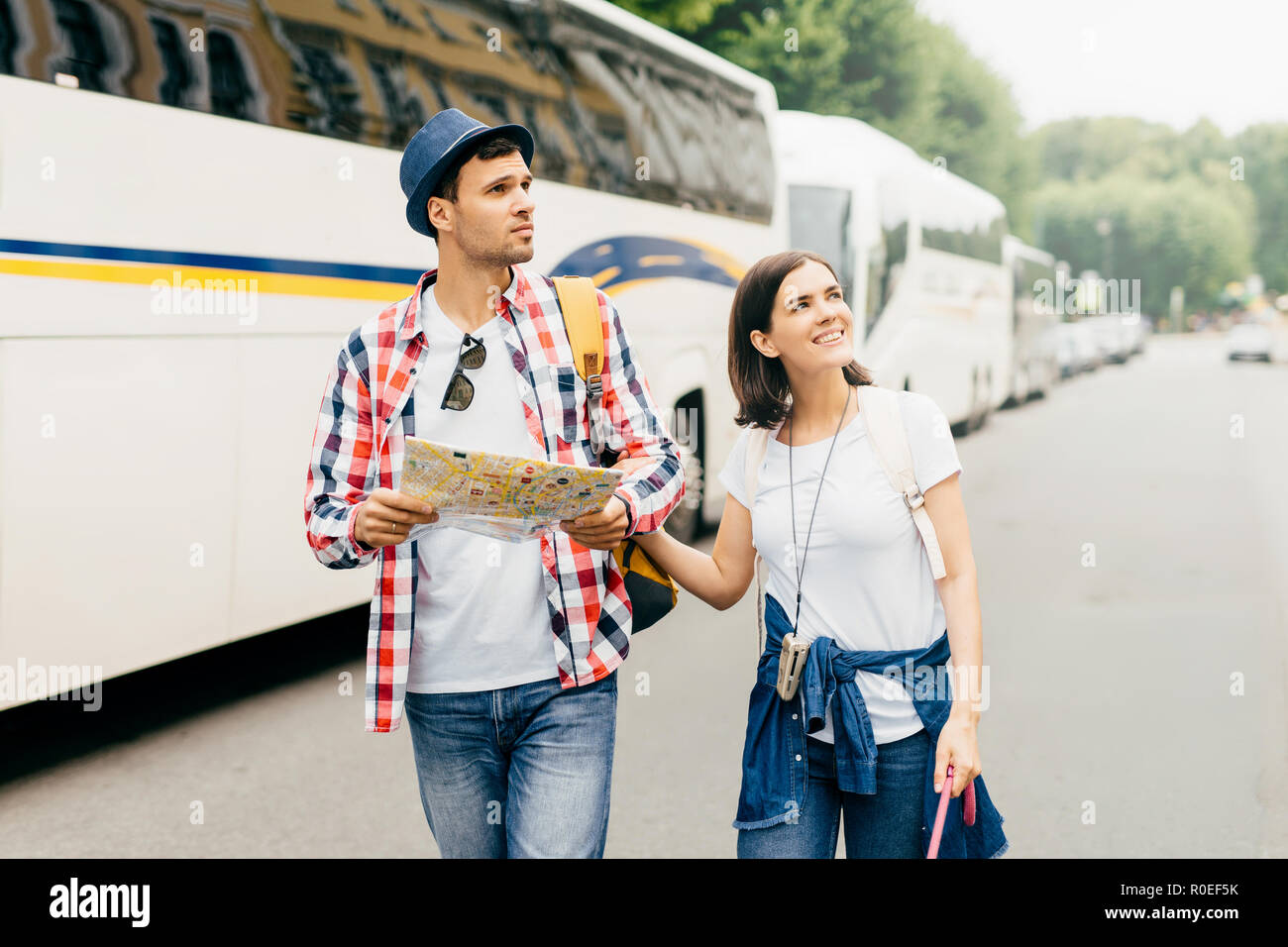 Young hiking couple going through big city, looking attentively aside, using city guide for exploration new places on map. Family couple having journe - Stock Image
