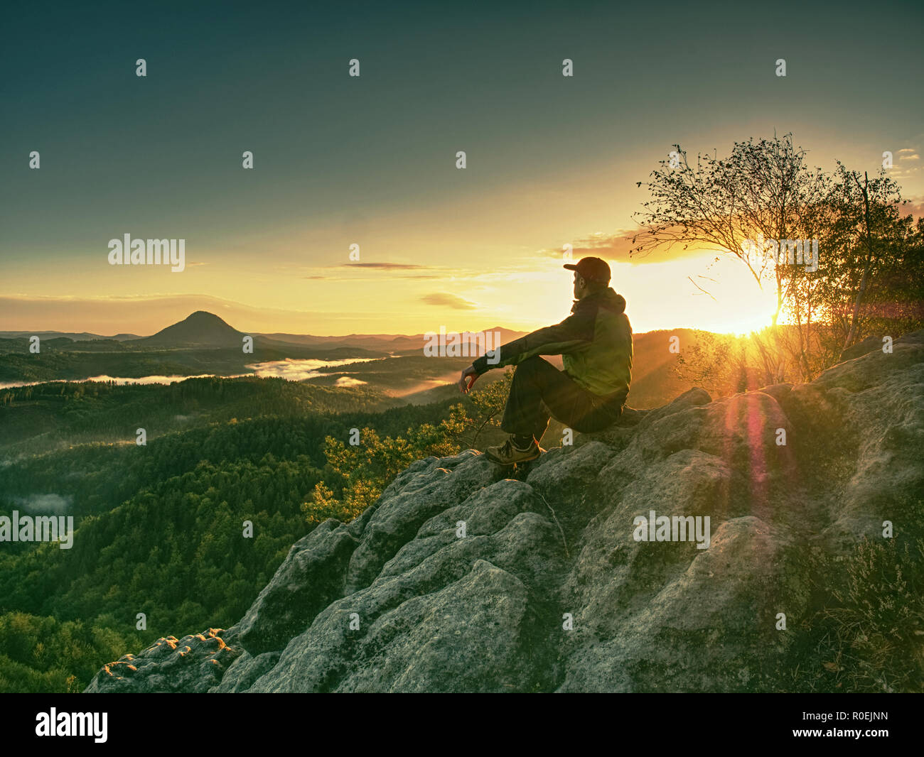 Crazy man at edge. Fearless hiker on cliff above deep hole. Morning or evening Sun close to horizon. Pure nature landscape - Stock Image