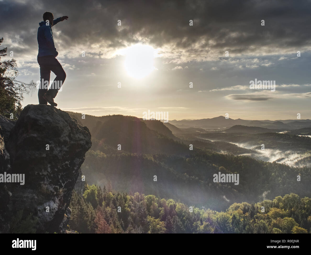 Man in rocks. Climbing hiking silhouette in fall mountains.  The climber in inspirational sunrise landscape on mountain peak. - Stock Image
