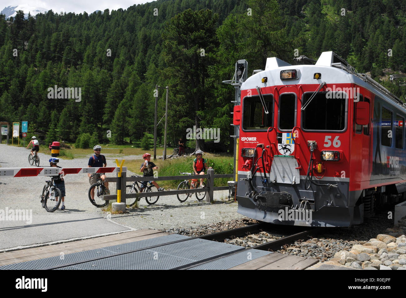 Swiss Alps: Bikers and hikers at the train station Morteratsch in Upper-Engadin in canton Graubünden - Stock Image