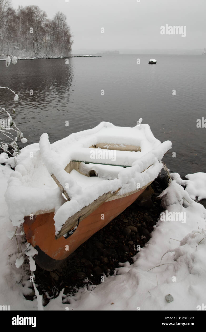 Early first snow has arrived and surprised the boat owner of this red rowing boat in Pyhäjärvi, Finland - Stock Image