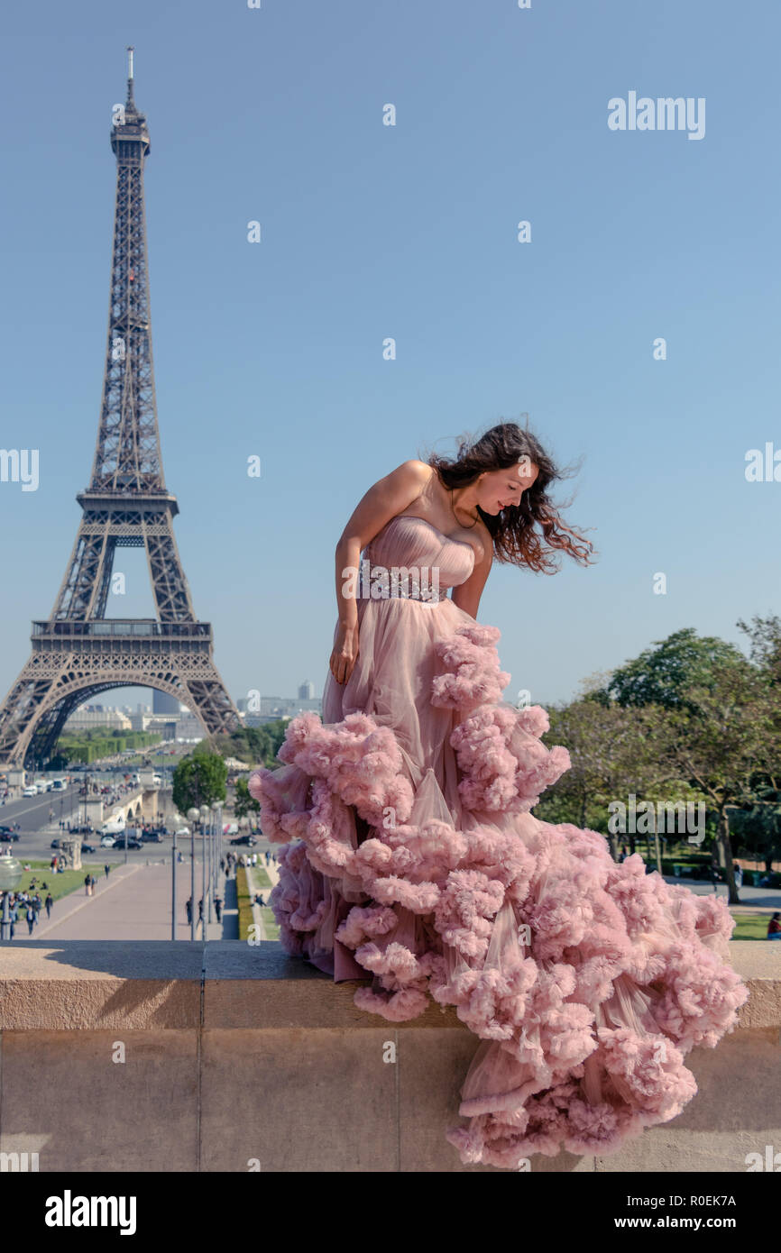 Beautiful hipster girl dressed to impress in a pastel pink ballroom dress with Eiffel Tower in background - Stock Image
