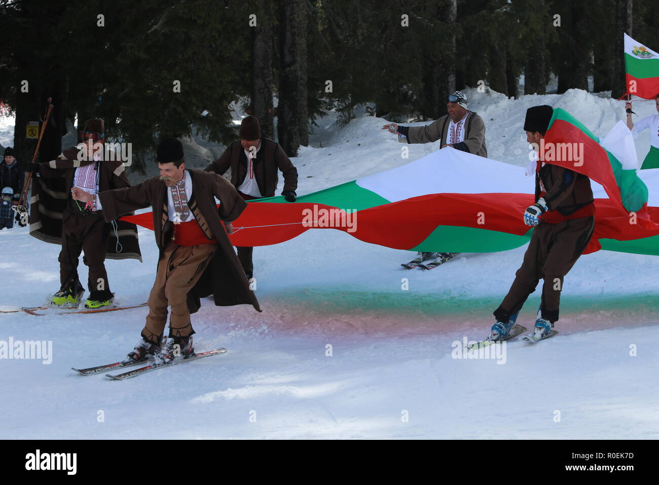 Skiing with Bulgarian flags at Pamporovo ski resort, Bulgaria. People dressed with traditional Bulgarian clothes skiing with the Bulgarian national fl - Stock Image