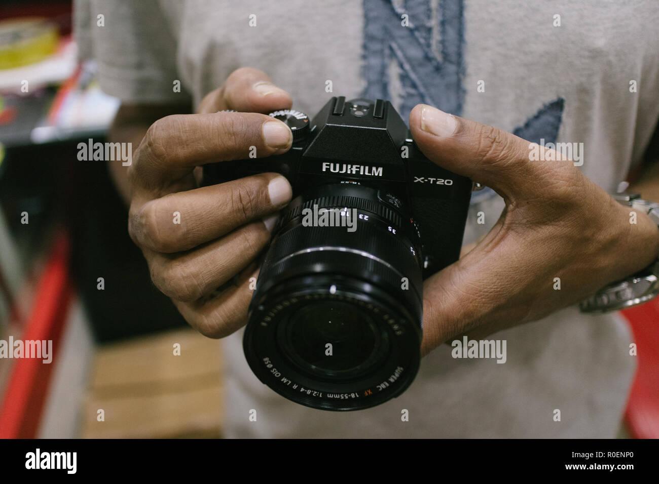 Indian customer checks brand new fujifilm X-t20 mirrorless camera at a camera store in Hyderabad,India - Stock Image