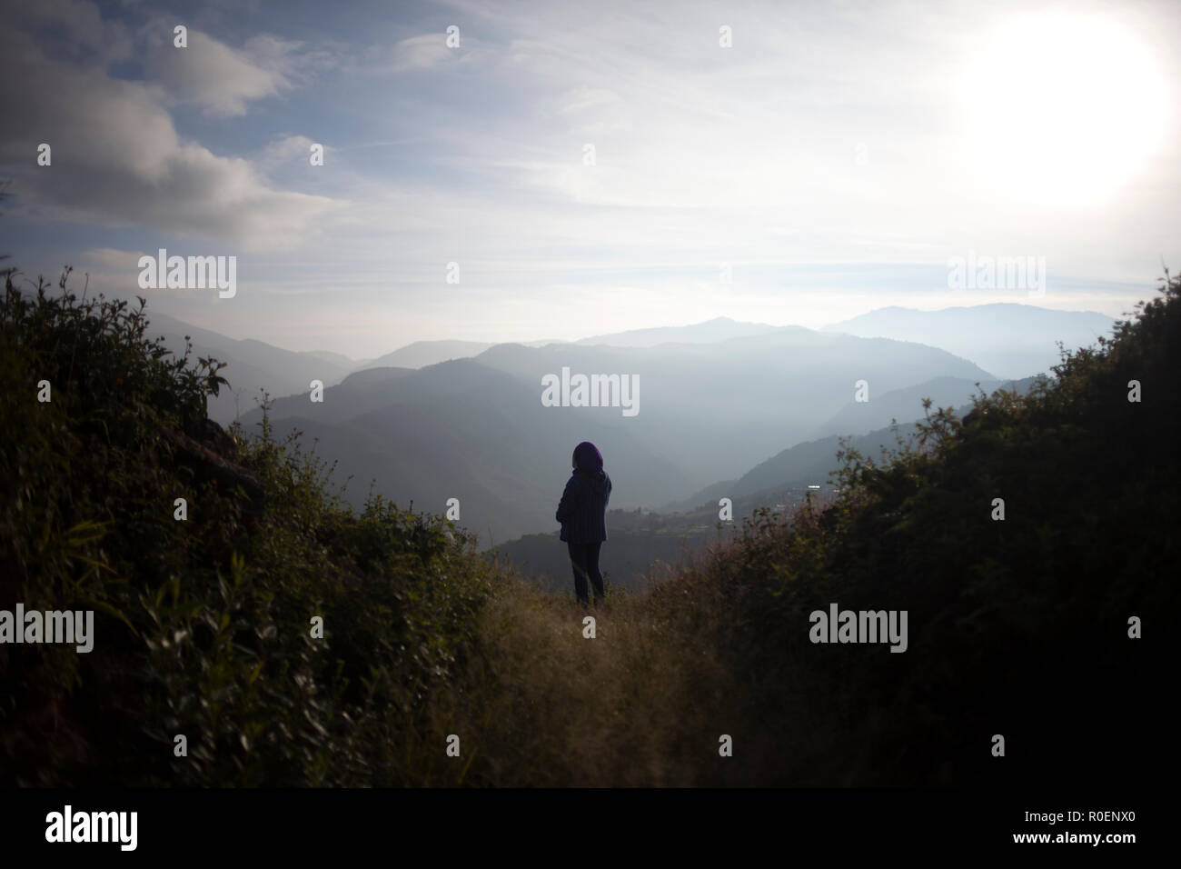 A woman walks at sunrise in Lachatao, in the Sierra Norte of Oaxaca, Mexico - Stock Image