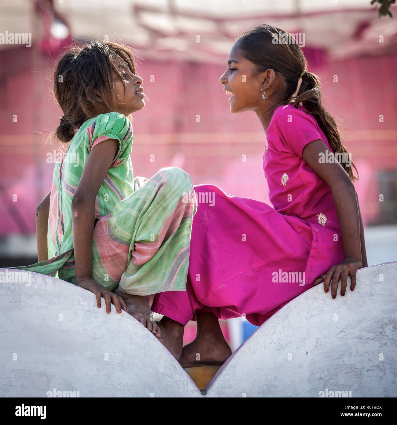 Two poor girls sitting on a wall, portrait, Pushkar, Rajasthan, India - Stock Image