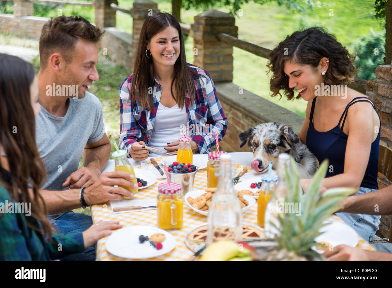 Group of happy people doing breakfast outdoors in a ...