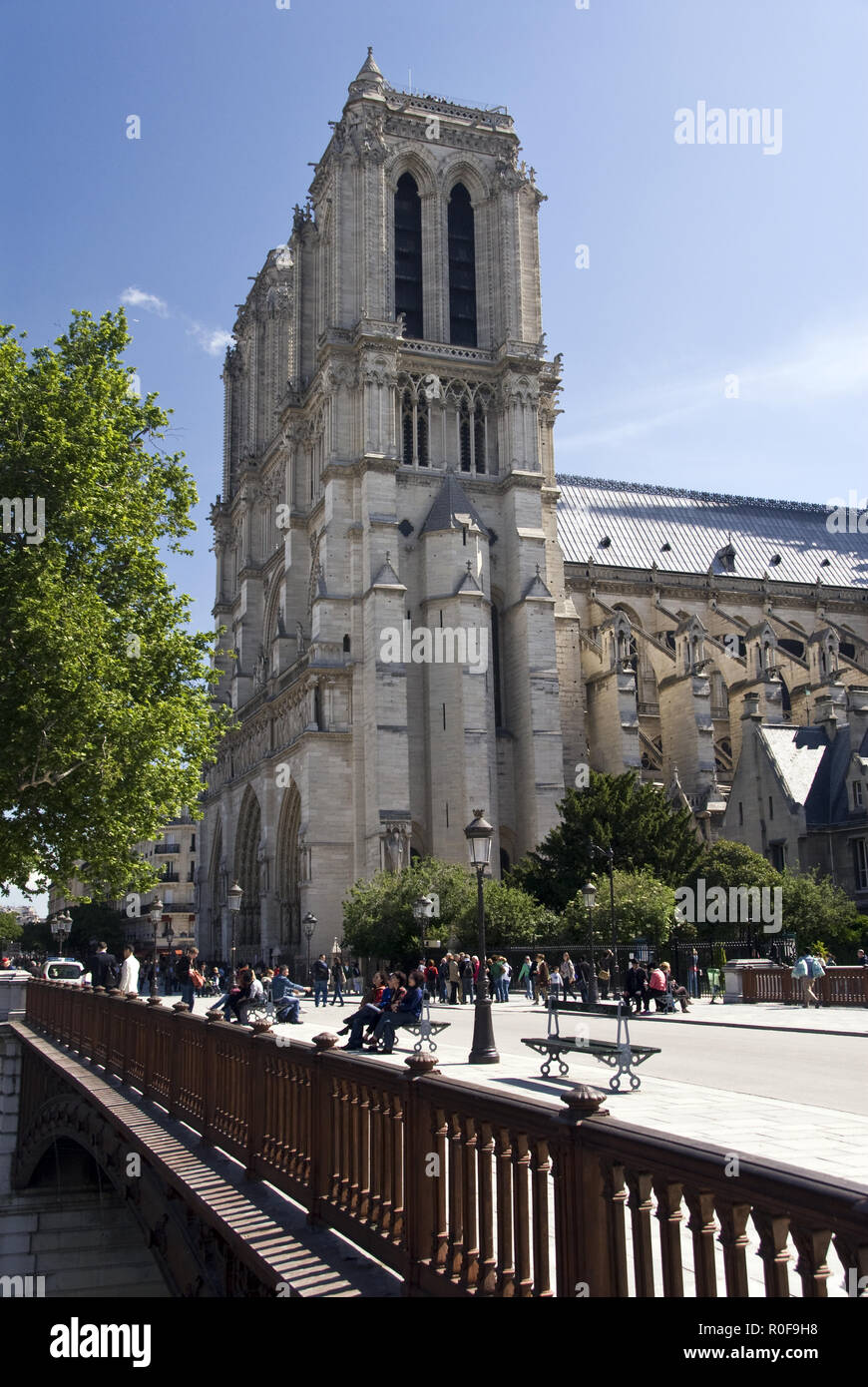 Tourists walk over the Pont au Double, which crosses the Seine river, to Notre Dame cathedral, in Paris, France. - Stock Image