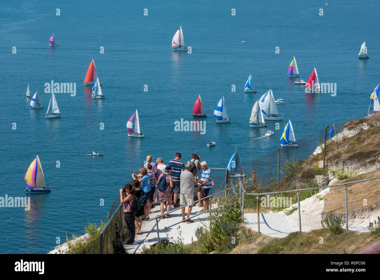 spectators and holiday makers watching the annual round the island yacht race at the needles viewpoint on the isle of wight. - Stock Image