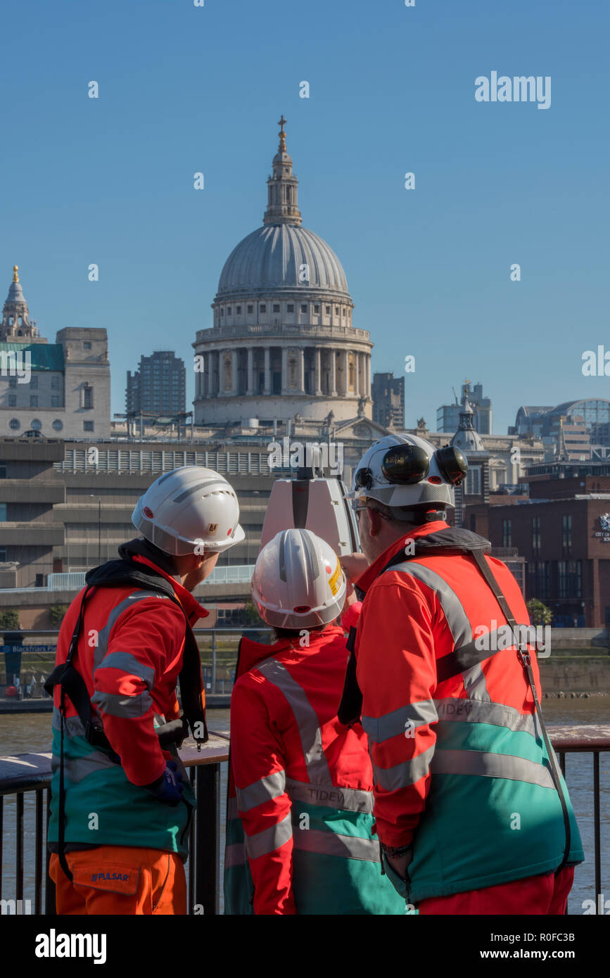 engineers dressed in high visibility clothing and hard hats surveying near the river thames and st paul's cathedral in central london. - Stock Image