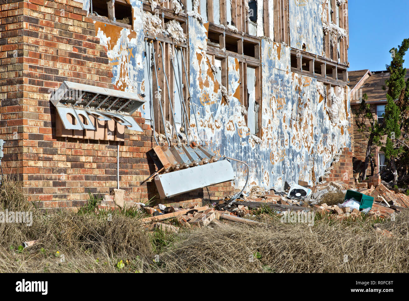 Destroyed exterior side wall of a six plex apartment unit, electric meter boxes & control panels, dislodged brick facing. - Stock Image
