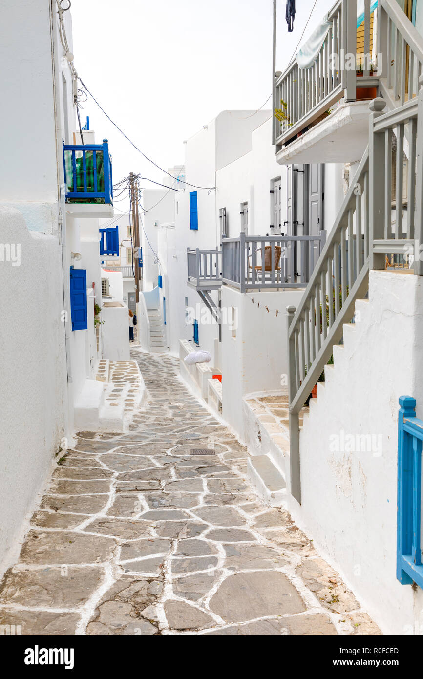 Traditional houses with blue doors and windows in the narrow streets of greek village in Mykonos, Greece Stock Photo