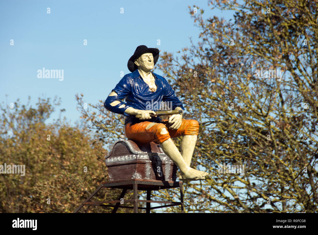 Model of poorly-dressed man sitting on trunk, with pistol in his hand, as 'Point of Sale' display outside closed shop, Hayling Island England - Stock Image