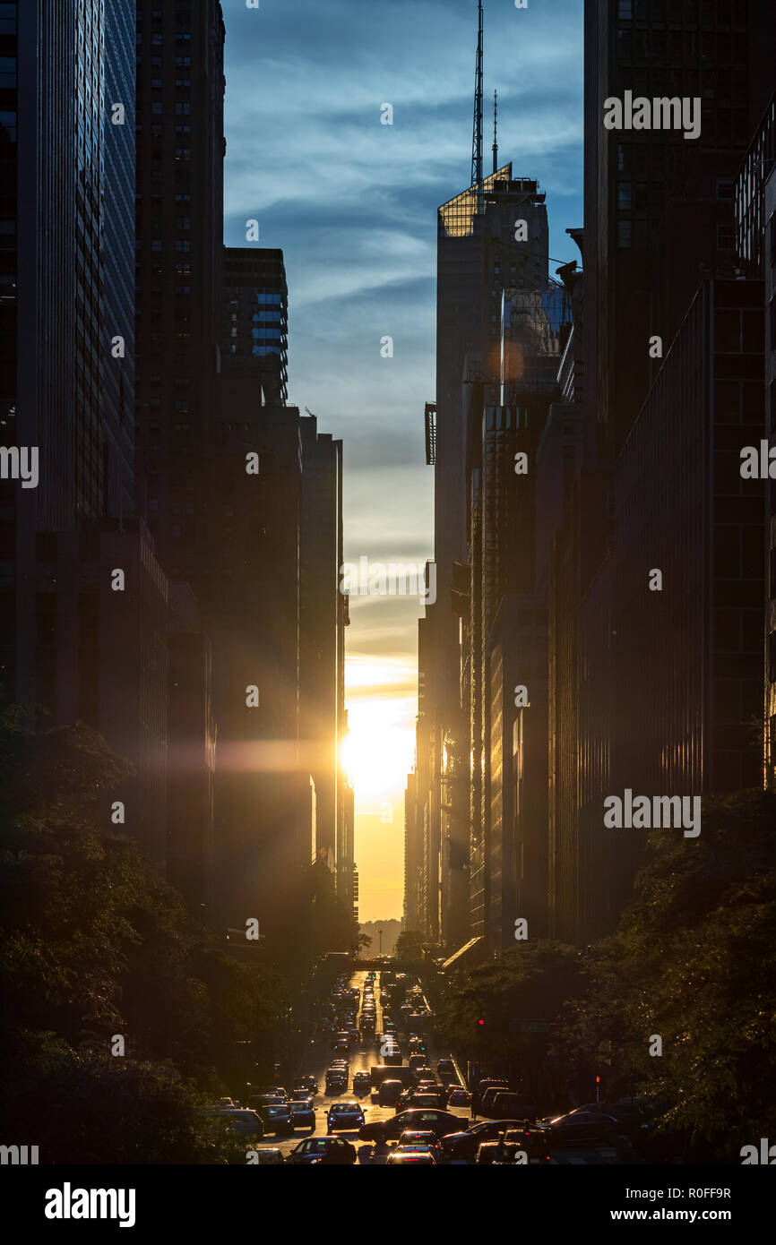 Sunset between the buildings of Midtown Manhattan with crosstown traffic along 42nd Street in New York City - Stock Image