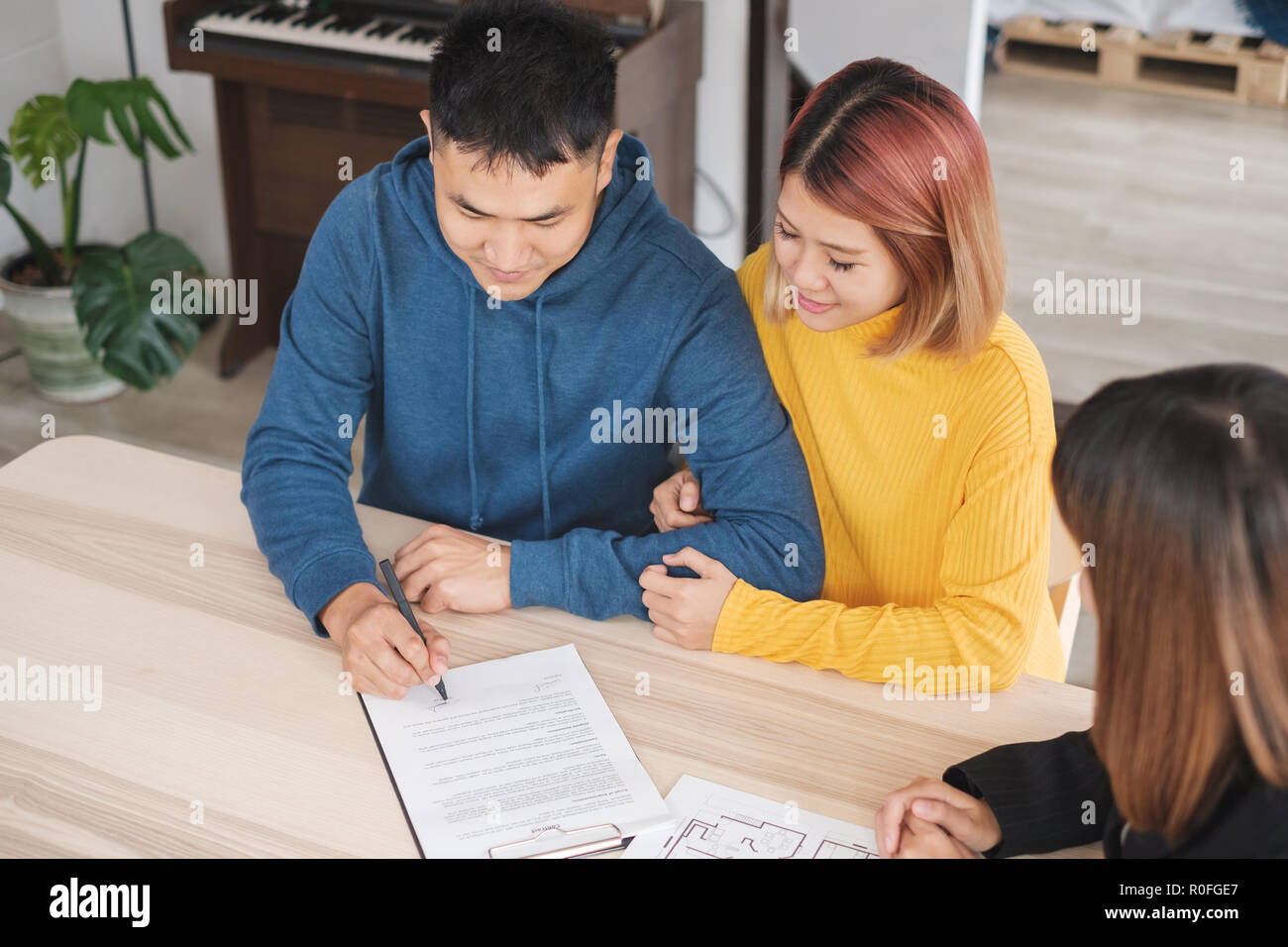 Asian happy couple sign contract buying new home with realtor agent with smiling face at new home.buying new house real estate Stock Photo