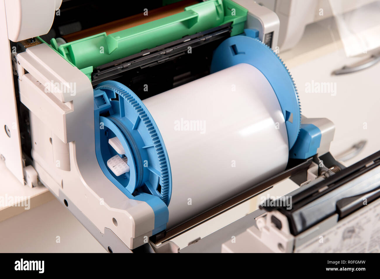 Used almost empty roll of photographic film paper on a printer in a printing house or studio in a closeup up view - Stock Image