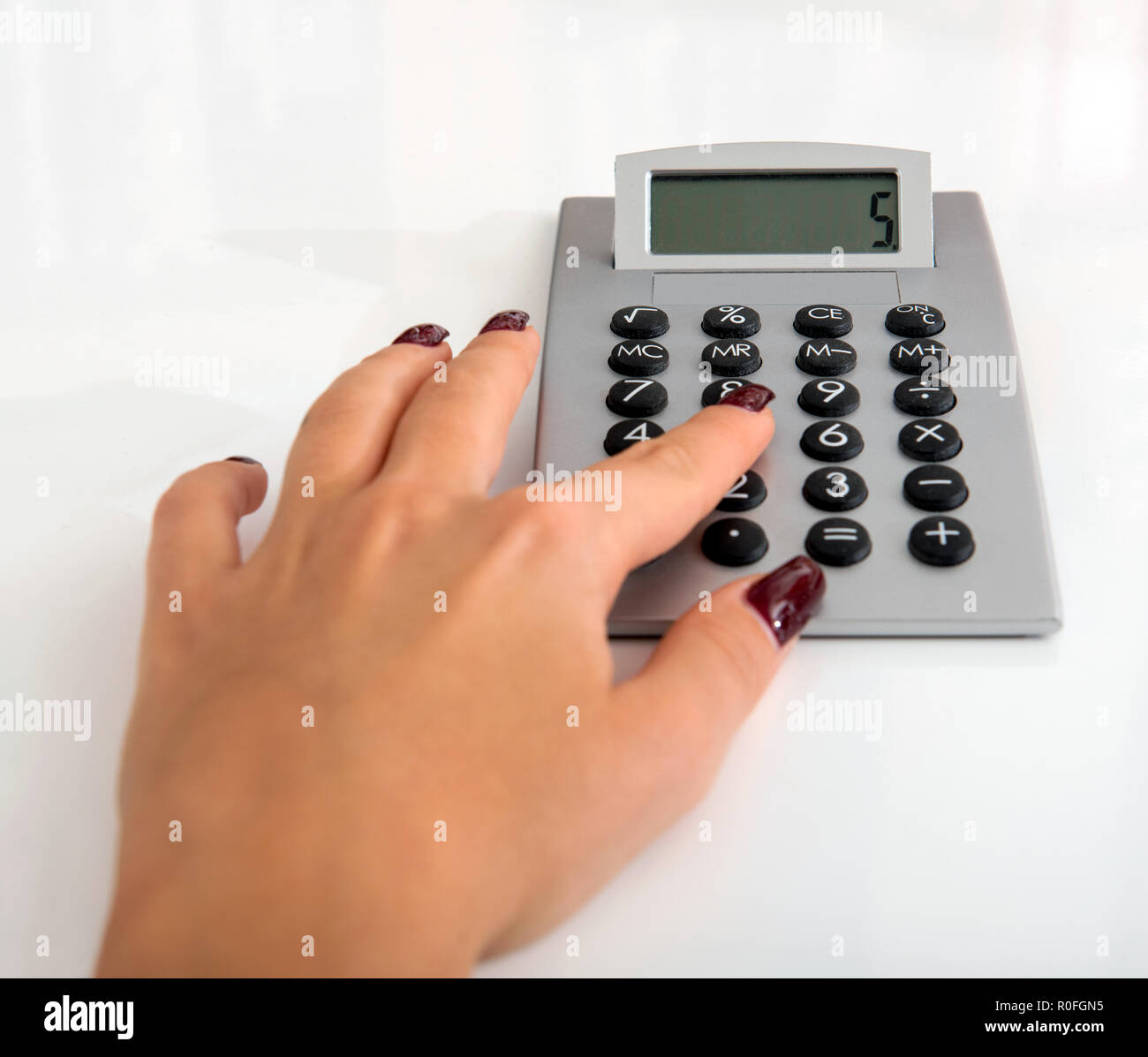 Woman pressing the number 5 on a manual desktop calculator while doing calculations for bookkeeping or accountancy in a close up view on white - Stock Image