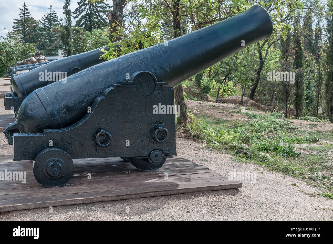 Old cannons on wooden carriages and defensive fort cores. Military - Stock Image