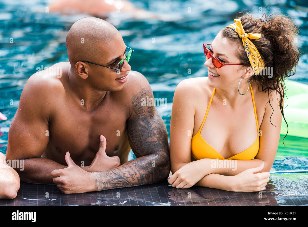 young in sunglasses looking at each other in swimming pool - Stock Image