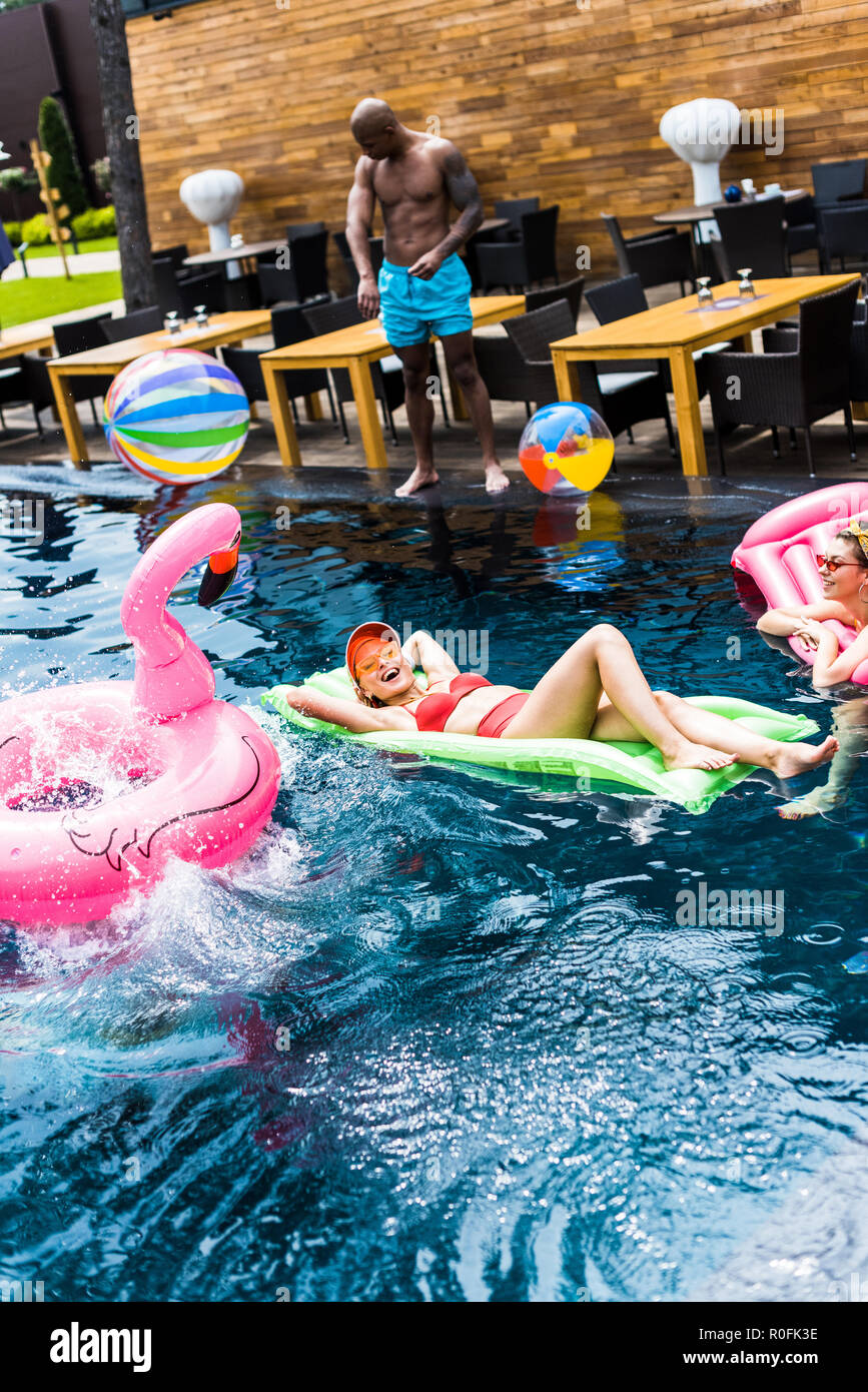 smiling women resting on inflatable mattresses in swimming pool - Stock Image