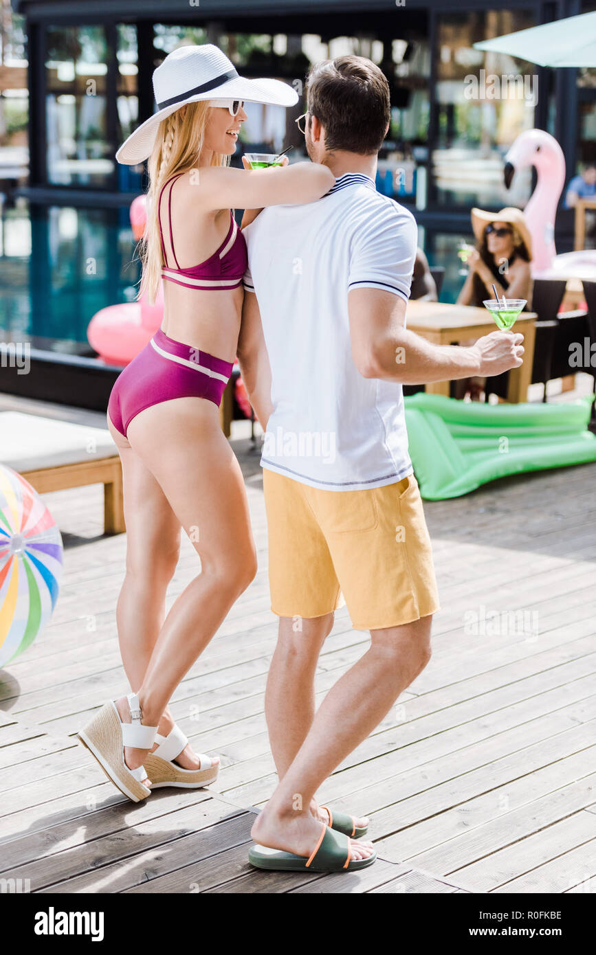 couple looking at each other and holding glasses of alcohol at swimming pool - Stock Image